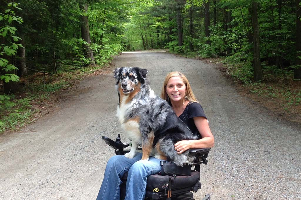 Woman and dog in wheelchair on gravel road