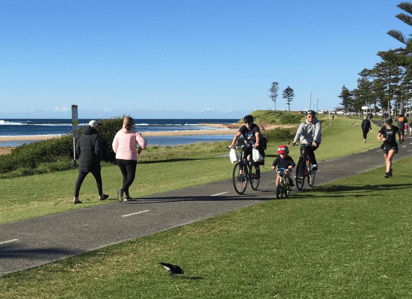 Families enjoying a shared seaside pathway